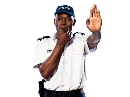"Portrait of an Afro American police officer holding a hand up to motion ""stop"" while blowing whistle on white background"