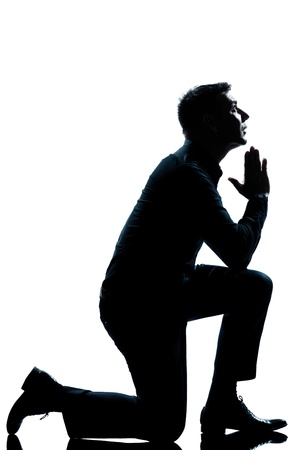 man praying: one caucasian man kneeling praying  full length silhouette in studio isolated white background