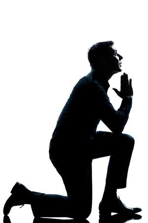 hombre orando: un hombre caucásico de rodillas orando silueta de cuerpo entero en el estudio de fondo blanco aislado Foto de archivo