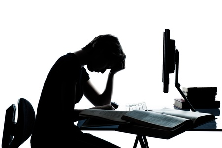one caucasian young teenager silhouette boy or girl studying with computer computing laptop tired sad despair in studio cut out isolated on white background photo