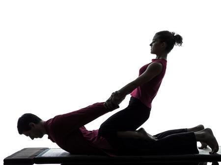homme massage: un homme et une femme perfoming massage tha� en studio silhouette sur fond blanc Banque d'images