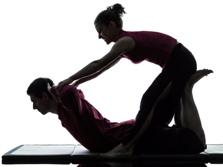 one man and woman perfoming thai massage in silhouette studio on white background photo