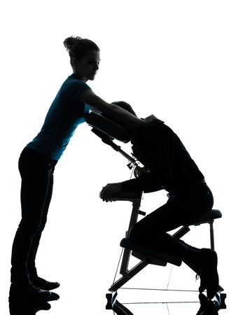 chair massage: one man and woman perfoming chair massage in silhouette studio on white background