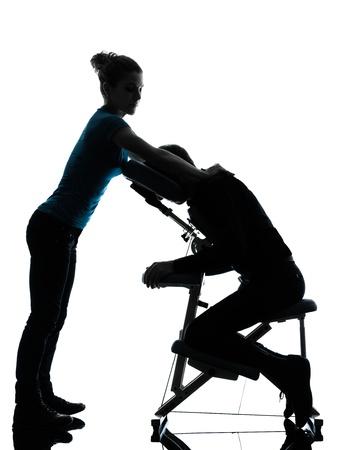 homme massage: un homme et une femme perfoming massage sur chaise en studio silhouette sur fond blanc