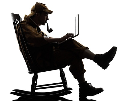rocking chair: sherlock holmes with computer laptop silhouette sitting in rocking chair in studio on white background Stock Photo
