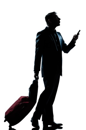 one caucasian business traveler man walking on the phone with suitcase  full length silhouette in studio isolated white background photo