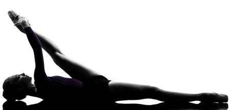 one caucasian young woman ballerina ballet dancer stretching warming up in silhouette studio on white background Stock Photo - 14903527