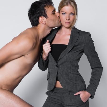 nude young: Молодая пара с человека в студии на изолированных серый фон с мужчина целует женщину в щеку