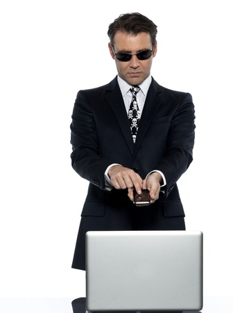 one criminal man computer hacker  caucasian computing on the phone  in studio isolated on white background photo
