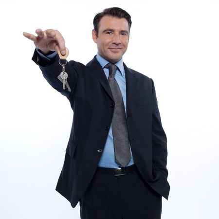 Realtor: one caucasian realtor man real estate agent businessman teasing holding offering keys isolated studio on white background