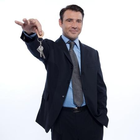 realtor: one caucasian realtor man real estate agent businessman teasing holding offering keys isolated studio on white background