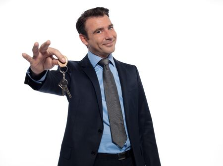 real estate people: one caucasian man real estate agent businessman teasing holding offering keys isolated studio on white background