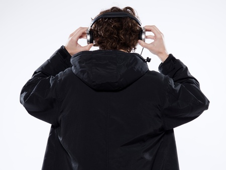 parka: studio portrait of a caucasian young man listening to music on white background Stock Photo