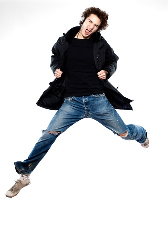 a young man: studio portrait of one  caucasian young man listening to music music jumping screaming isolated on white background Stock Photo