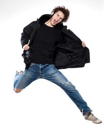 springende mensen: studio portret van een Kaukasische jonge man luisteren naar muziek muziek springen gillen geïsoleerd op witte achtergrond Stockfoto