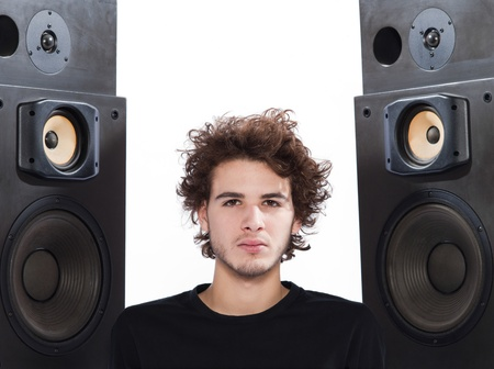 stereo cut: studio portrait of a one caucasian young man listening to music lover with speakerphones isolated on white background Stock Photo