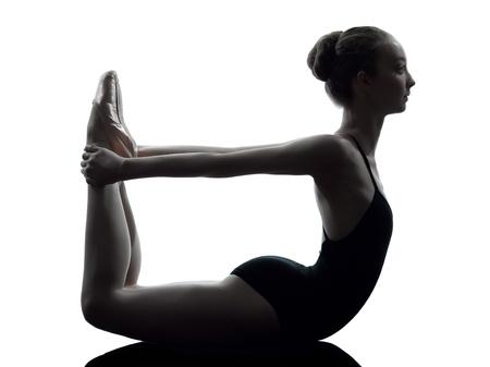 bailarines silueta: una mujer caucásica joven bailarina de ballet bailarina estiramiento de calentamiento en el estudio de la silueta en el fondo blanco