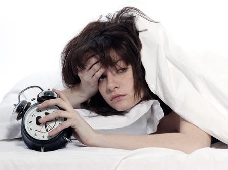 agotado: mujer joven en cama cansado despertar reloj celebraci�n alarma sobre fondo blanco
