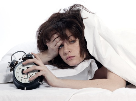 hangover: young woman woman in bed awakening tired holding alarm clock on white background