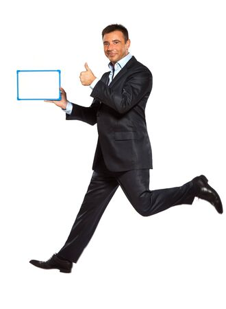 one caucasian business man running jumping double thumbs up holding whiteboard in studio isolated on white background photo