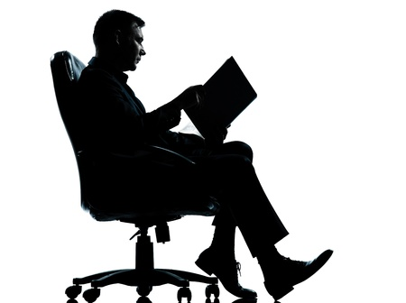 one caucasian business man sitting in armchair reading ancient book silhouette Full length in studio isolated on white background photo