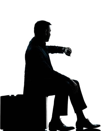 looking at watch: one caucasian business man sitting on suitcase checking time silhouette Full length in studio isolated on white background