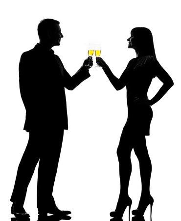 siluetas de enamorados: un hombre cauc�sico y mujer bebiendo champ�n en la fiesta de tostado estudio silueta aislados sobre fondo blanco
