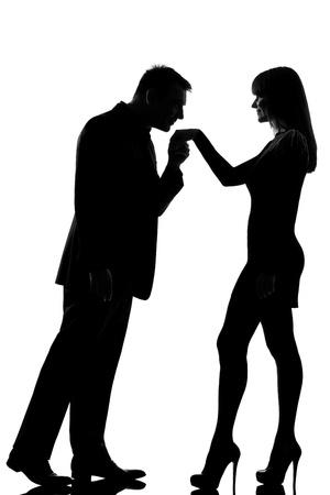 siluetas de enamorados: un hombre cauc�sico que besa mano de la mujer en el estudio de la silueta aislado en el fondo blanco Foto de archivo