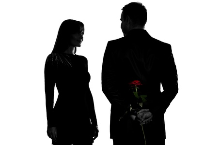 two women and one man: one caucasian couple man and woman smiling in studio silhouette isolated on white background