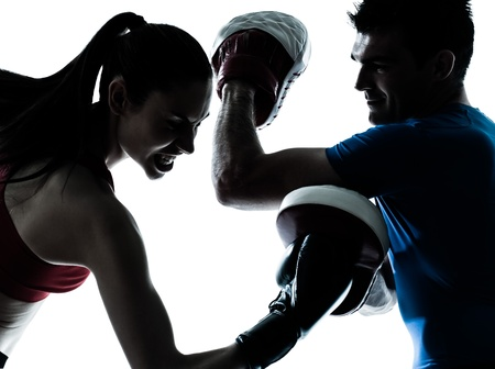 personal trainer: personal trainer man coach and woman exercising boxing silhouette  studio isolated on white background