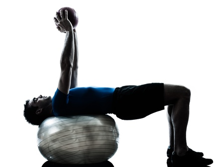one caucasian man exercising workout fitness ball in silhouette studio  isolated on white background Stock Photo - 15480376