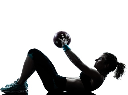 exercising: one caucasian woman exercising fitness ball workout posture in silhouette studio isolated on white background