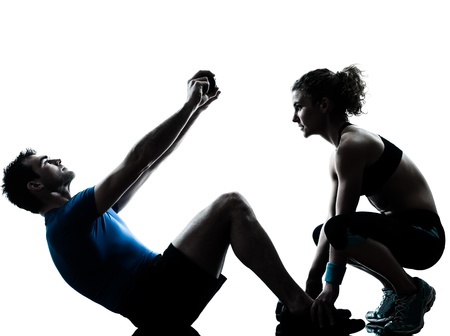 aerobic training: one caucasian couple man woman personal trainer coach exercising abdominal silhouette studio isolated on white background