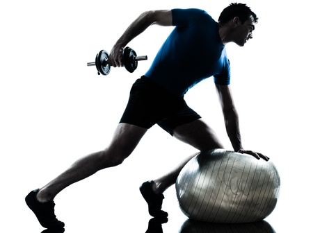 fitness ball: one caucasian man exercising weight training workout fitness in silhouette studio  isolated on white background