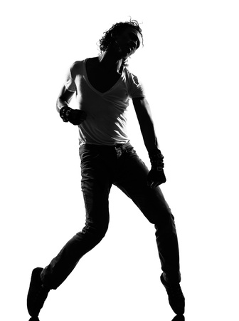 tiptoe: full length silhouette of a young man dancer dancing funky hip hop and r&b on  isolated  studio white background Stock Photo