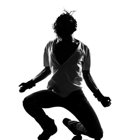 silueta de cuerpo entero de un hombre joven bailarín de hip hop bailando cobarde r & b en estudio aislado fondo blanco