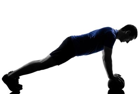 gimnasia aerobica: hombre que ejercita aptitud del entrenamiento de empuje ups postura aer�bic en el estudio de la silueta aislado en el fondo blanco Foto de archivo
