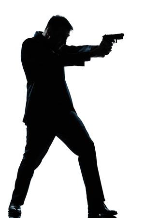 hombre disparando: un espía caucásico policía criminal detective hombre silueta tiro apuntando la pistola de larga duración en estudio de fondo blanco aisladas
