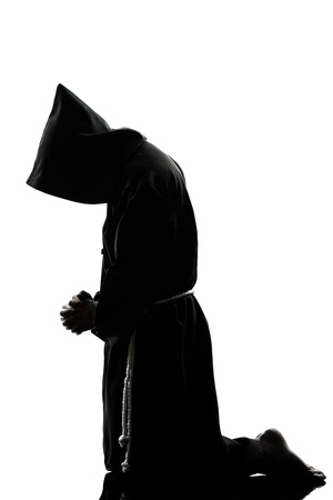 man kneeling: one caucasian man priest praying silhouette in studio isolated on white background Stock Photo