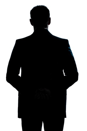 man rear view: one caucasian man portrait silhouette backside standing hands behind back in studio isolated white background Stock Photo
