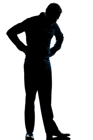 standing out: one caucasian man  looking at his shoes full length silhouette in studio isolated white background