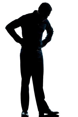 silueta hombre: un hombre cauc�sico que mira sus zapatos silueta de cuerpo entero en el estudio de fondo blanco aislado