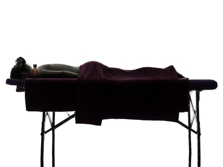 massage table: one woman lying on a massage table in silhouette studio on white background