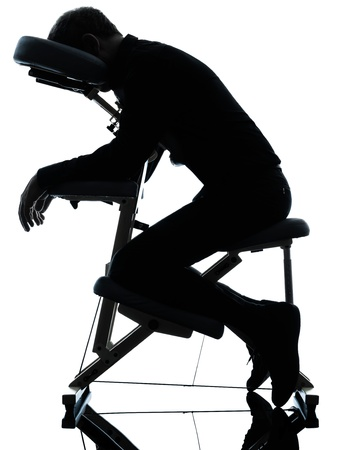 chair massage: one man on chair massage in silhouette studio on white background