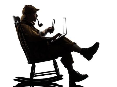 investigacion: sherlock holmes con la silueta del ordenador portátil sentado en una mecedora en el estudio sobre fondo blanco