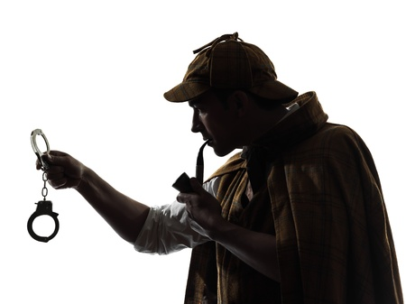 sherlock holmes holding handcuffs silhouette in studio on white background photo