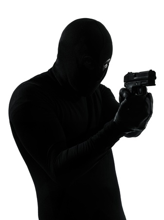 man holding gun: thief criminal terrorist holding gun portrait in silhouette studio isolated on white background Stock Photo