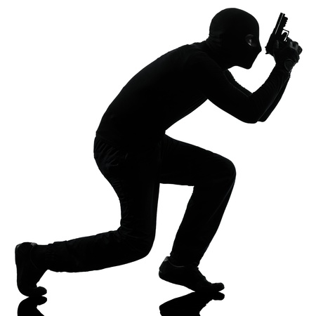 man holding gun: thief criminal terrorist in silhouette studio isolated on white background