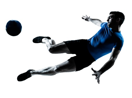 action shot: one caucasian man flying kicking playing soccer football player silhouette  in studio isolated on white background Stock Photo
