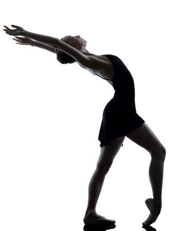 ballet clásico: una mujer caucásica joven bailarina de ballet bailarina estiramiento de calentamiento en el estudio de la silueta en el fondo blanco